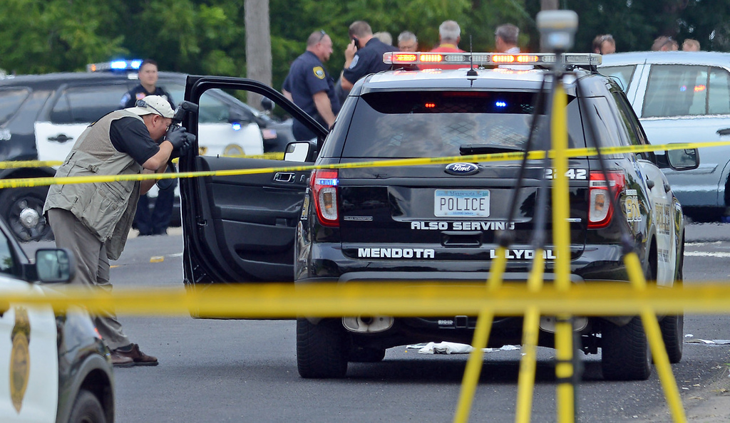 . An officer with the Minnesota Bureau of Criminal Apprehension photographs an SUV that was driven by  Mendota Heights Police Officer Scott Patrick, who was shot and killed at 12:20 PM during a traffic stop near the intersection of Dodd Road and Smith Avenue in West St. Paul on Wednesday. (Pioneer Press: Ben Garvin)