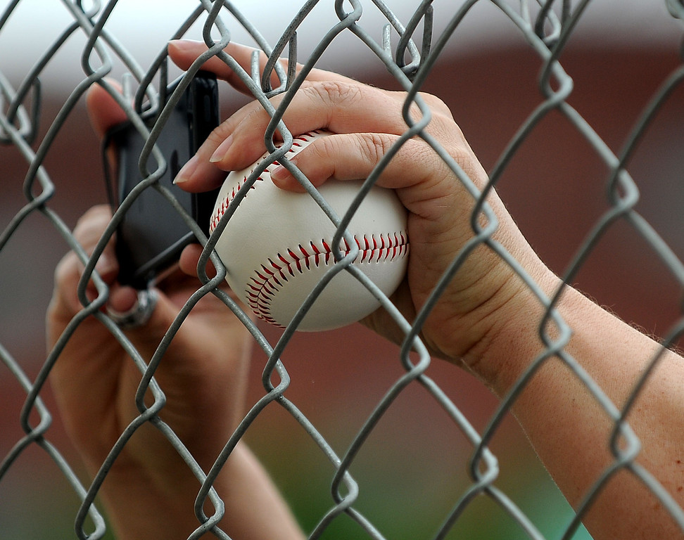 . A lucky Saint Paul Saints with a new free baseball takes a photo of the demo site with a cell phone.  (Pioneer Press: Sherri LaRose-Chiglo)