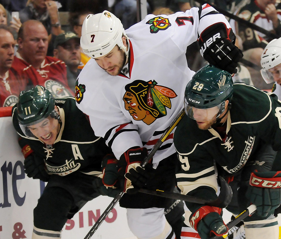 . Minnesota left wing Zach Parise, left, right wing Jason Pominville, right, and Chicago defenseman Brent Seabrook battle for a puck behind the Chicago net in the third period. (Pioneer Press: John Autey)