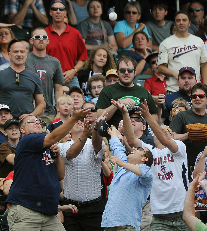 . Fans reach for a Joe Mauer foul ball during the seventh inning. (Pioneer Press: John Autey)