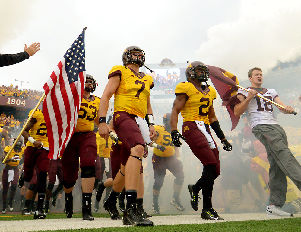 . Minnesota quarterback Mitch Leidne, center, defensive back Cedric Thompson, right, and offensive lineman Luke Rasmussen lead the Gophers onto the field before the game.  (Pioneer Press: John Autey)