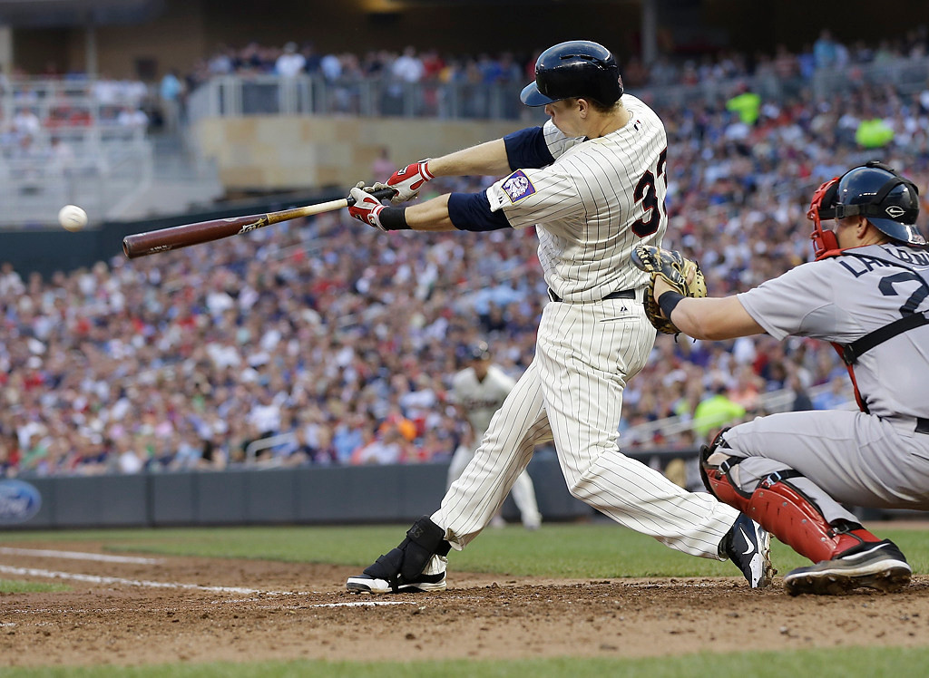 . Minnesota Twins\' Justin Morneau hits an RBI single off Boston Red Sox pitcher Ryan Dempster in the fourth inning. (AP Photo/Jim Mone)