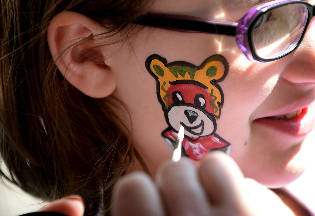 ". 11-year-old Pearl Larson of Coon Rapids, holds still as Deb Peitso of Maund Entertainment paints ""Nordy\"" on her face during the Game 3 block party. (Pioneer Press: Sherri LaRose-Chiglo)"