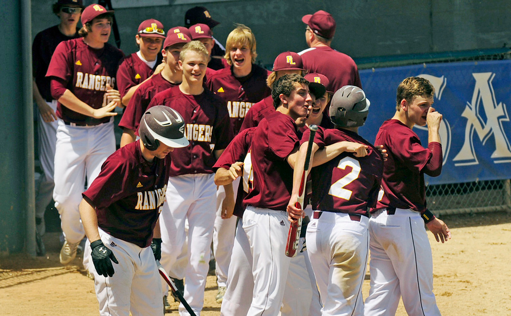 . Forest Lake players celebrate a run scored by Reid Larson (#2), who came home on a single by teammate Beau Fandel ito tie the game in the fifth inning against Mounds View.  (Pioneer Press: Scott Takushi)