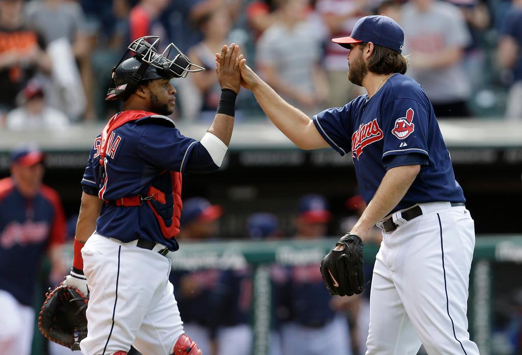 . Cleveland Indians catcher Carlos Santana, left, congratulates relief pitcher Chris Perez after the Indians defeated the Minnesota Twins 7-3. (AP Photo/Tony Dejak)