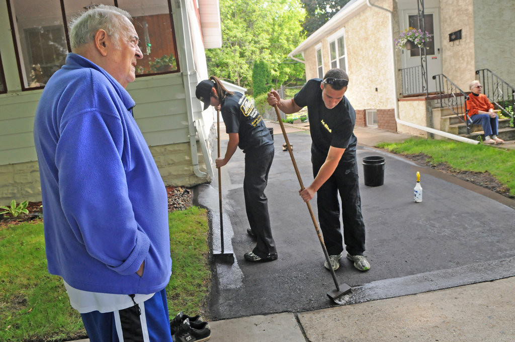. Bob Kuehn, left, and his wife, Opal, far right, watch a crew from Jet-Black reseal their driveway for free. (Pioneer Press: Jean Pieri)