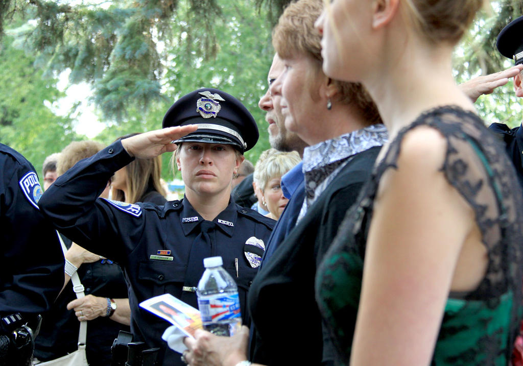 . Mendota Heights police officer Jennifer Fordham salutes as Michelle Patrick and her family pass outside St. Stephen\'s Lutheran Church following the funeral service for officer Scott Patrick in West St. Paul on Wednesday, August 6, 2014.  (Minnesota Department of Public Safety Pool Photo: Jen Longaecker)