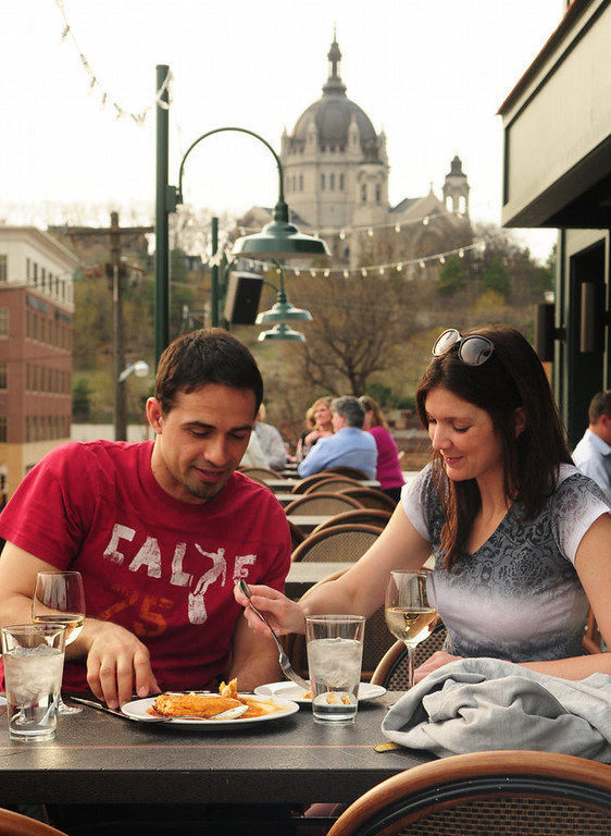 ". John Gonzalez of St. Paul and Talina Rauch of Eden Prairie enjoy ""spiedini di mozzarella,\"" a fried mozzarella appetizer, on the patio at Louis, the new restaurant atop Cosetta, on May 6, 2013. (Pioneer Press: Scott Takushi)"