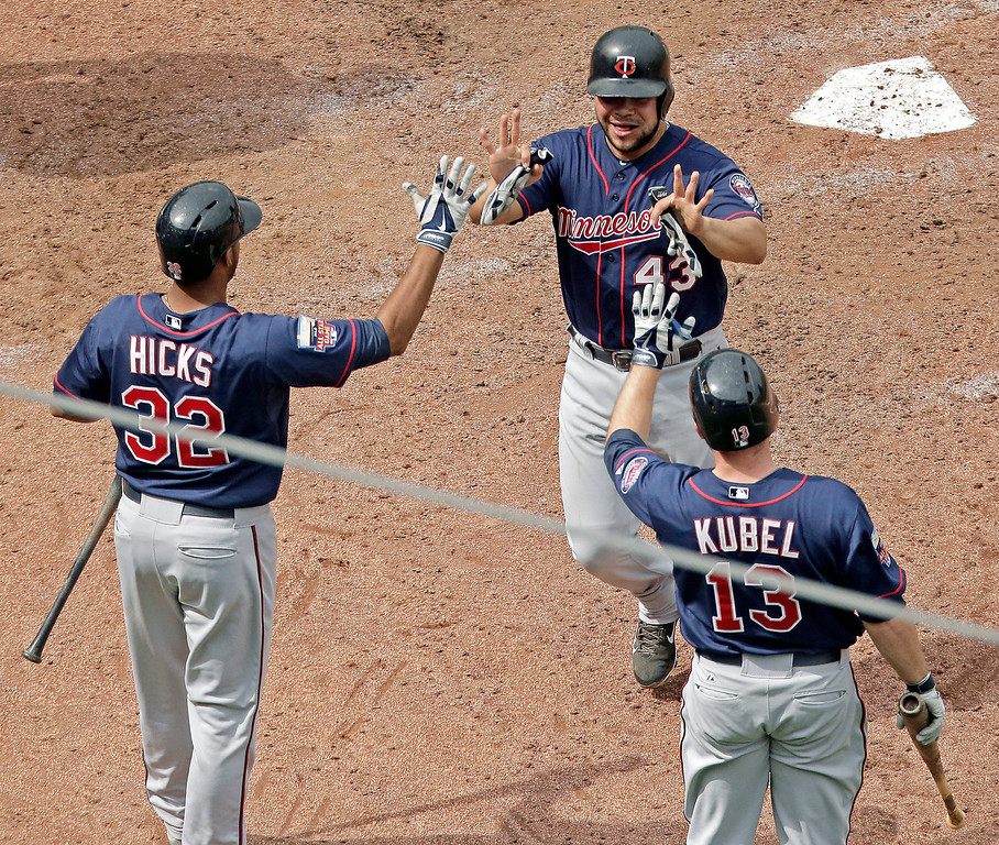 . Minnesota Twins\' Josmil Pinto (43), Jason Kubel (13) and Aaron Hicks (32) celebrate after Pinto and Kubel scored on a two-run double hit by Kurt Suzuki during the seventh inning. (AP Photo/Charlie Riedel)