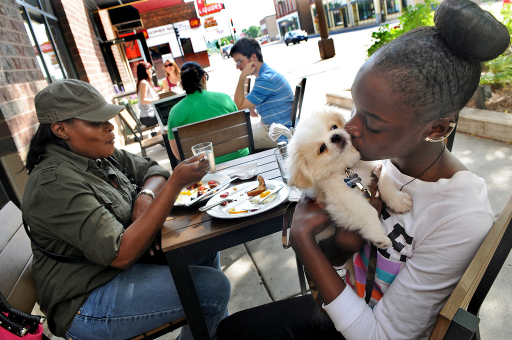 . Demeshe Baker, 11, right, kisses Snowball, her Pekingese, while her mom, Vikki Johnson of Minnetonka, finishes her meal at an outdoor table at the Buttered Tin. (Pioneer Press: Jean Pieri)