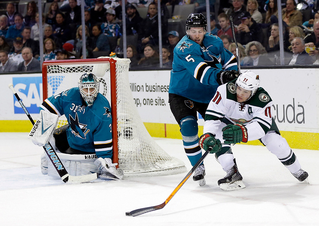 . Minnesota Wild\'s Zach Parise (11) reaches for the puck as San Jose Sharks\' Jason Demers (5) defends during the second period of an NHL hockey game on Saturday, Jan. 25, 2014, in San Jose, Calif. (AP Photo/Marcio Jose Sanchez)