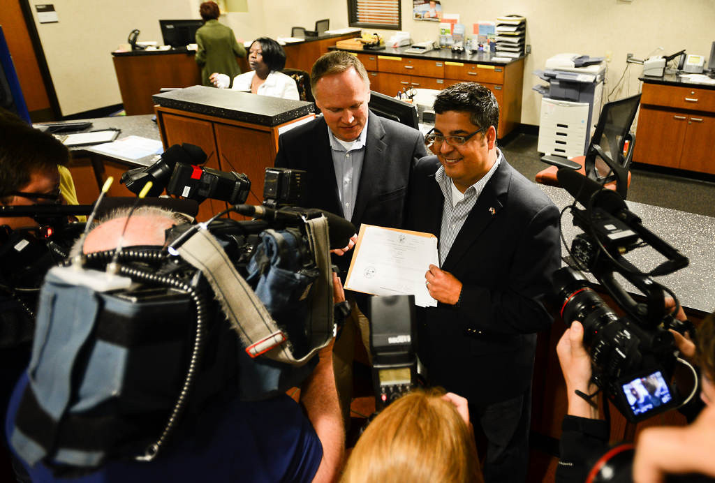 """. Jeff Isaacson, left, and his partner Al Giraud, seen here holding up their application for the gathered media, were the first couple in Hennepin County to file their marriage application on Thursday. \""""This is history, we didn\'t want to waste any time,\"""" said Isaacson. (Pioneer Press: Ben Garvin)"""