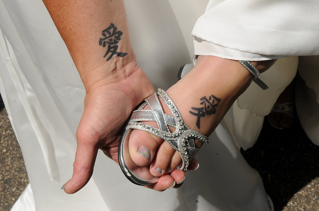 ". Shirley Otto, left, and Rochelle ""Shay\"" Imdieke show their tattoos of the symbol of love in Chinese. Otto has her tattoo on her right arm; Imdieke has her tattoo on her foot.  (Pioneer Press: Jean Pieri)"