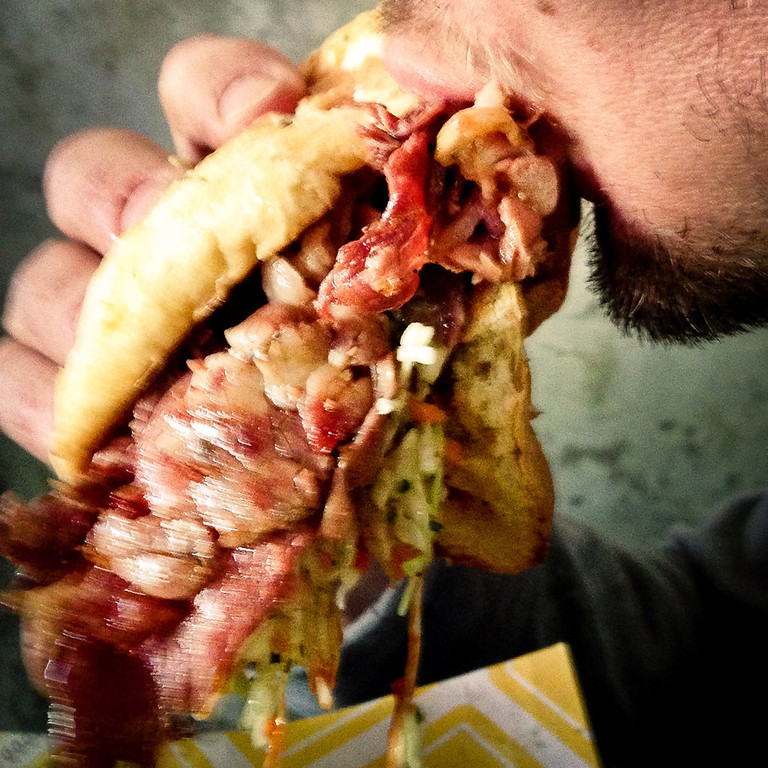 . Andrew Zimmern\'s $12 smoked meat sandwich is snarfed by this hungry fan between innings. (Pioneer Press: Ben Garvin)
