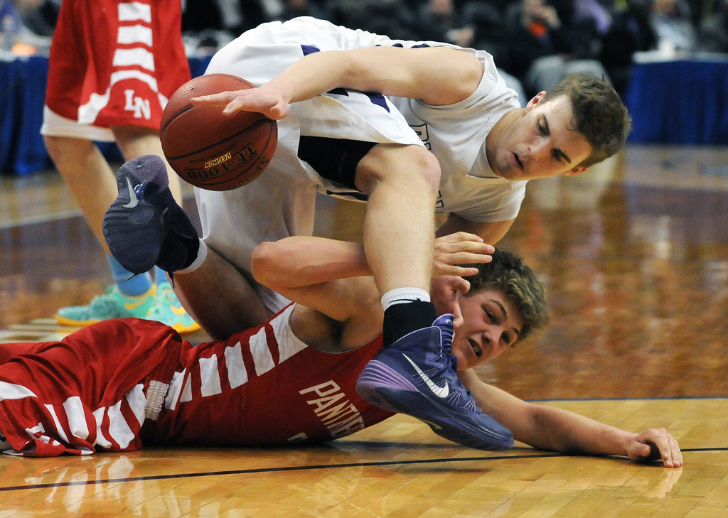 . Buffalo\'s Levi Bean falls on Lakeville North\'s Calven Pesola as they fight for a loose ball in the second half.  (Pioneer Press: Scott Takushi)