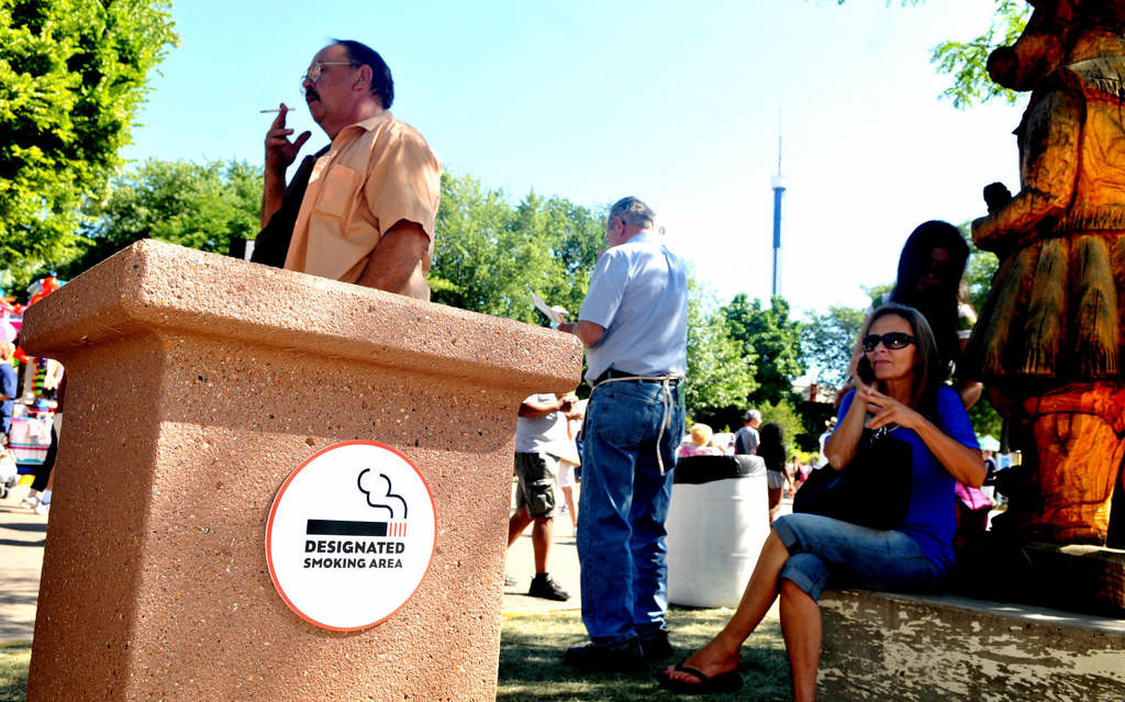. Smokers gather around a big cement ashtray in the smoking area in front of the Dairy Building. Designated smoking areas are identified with signs and include seating. (Pioneer Press: John Doman)