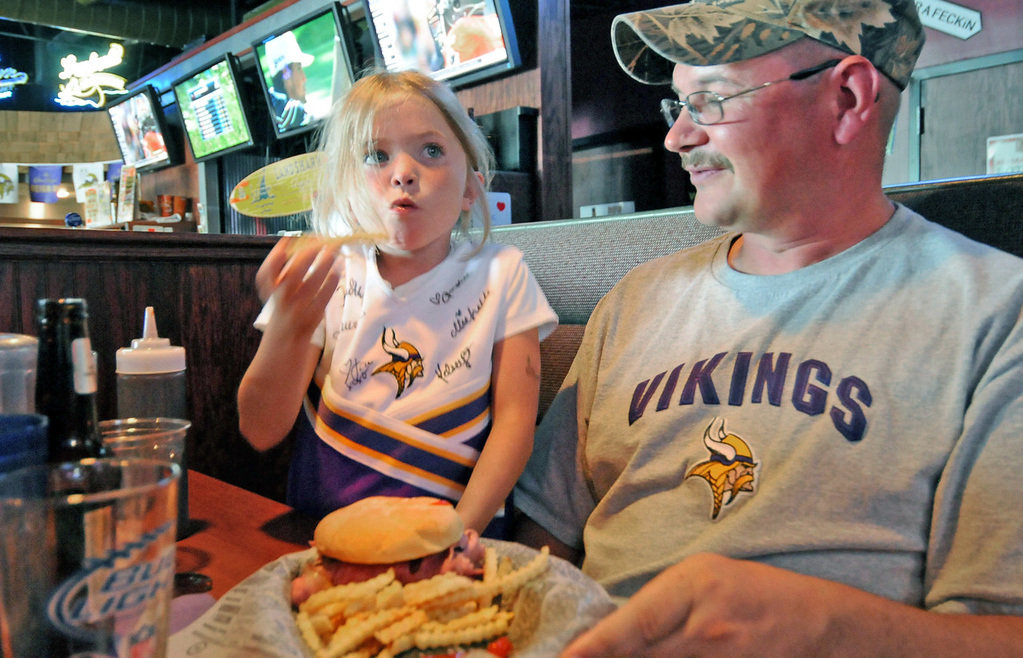 . Vikings fans Ella Gustafson, 5, of Renville and her dad Jim grab a bite to eat at Johnny B\'s restaurant in Mankato before a team scrimmage Saturday afternoon. (Pioneer Press: Sherri LaRose-Chiglo)