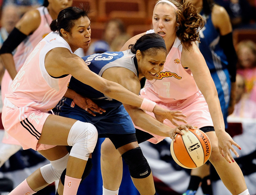 . Minnesota Lynx\'s Maya Moore, center is pressured by Connecticut Sun\'s Iziane Castro Marques, left, and Kayla Pedersen, right, during the second half. (AP Photo/Jessica Hill)