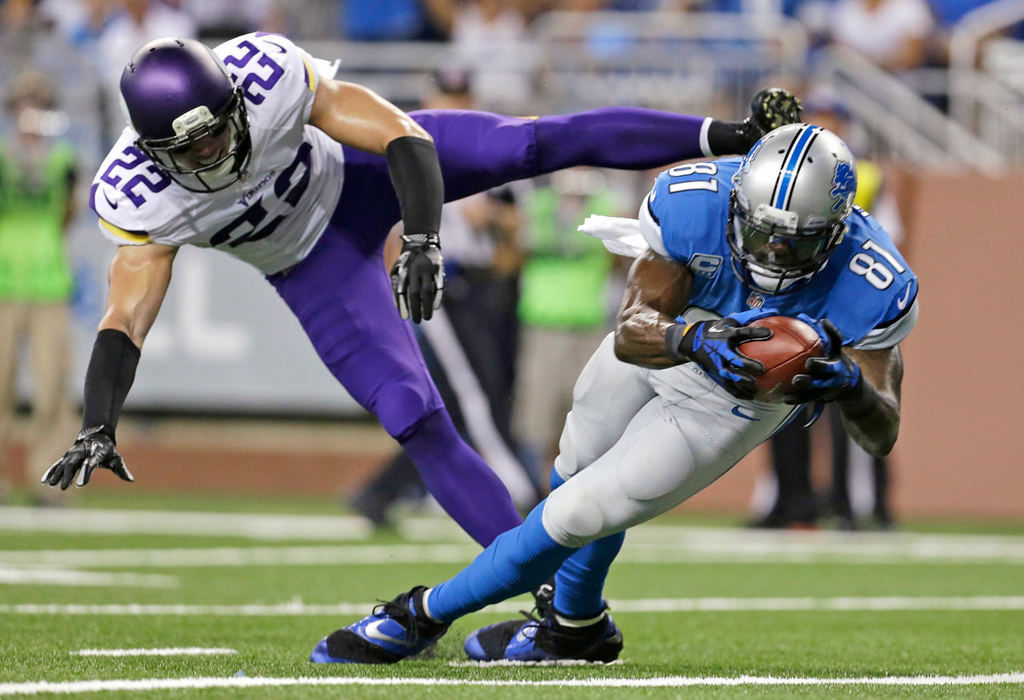 . Lions wide receiver Calvin Johnson, right, makes a catch while defended by Vikings free safety Harrison Smith during the first quarter. (AP Photo/Paul Sancya)