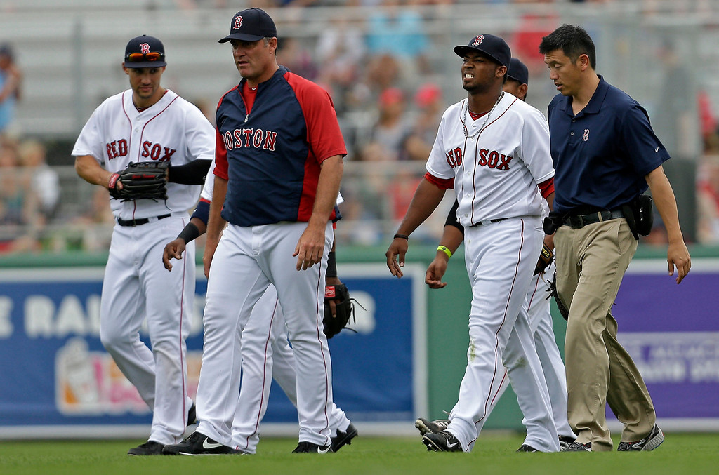 . Boston Red Sox manager John Farrell, second left, walks off the field with outfielder Keury De La Cruz, second right, was injured diving for a pop fly during an exhibition baseball game against the Minnesota Twins in Fort Myers, Fla., Saturday, March 29, 2014. (AP Photo/Gerald Herbert)