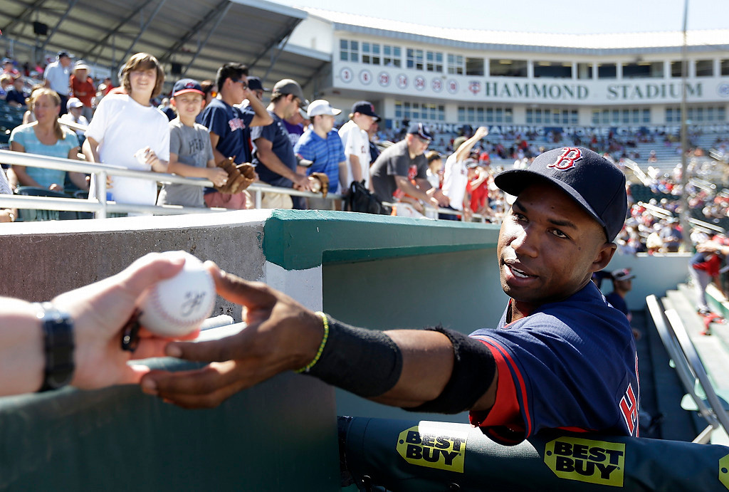 . Boston Red Sox second baseman Jonathan Herrera, right, signs autographs for fans before an exhibition baseball game against the Minnesota Twins, Saturday, March 1, 2014, in Fort Myers, Fla. (AP Photo/Steven Senne)
