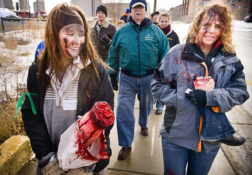 . Mock amputees Becky Maki of Minneapolis, left, and Emily Chrysler of Richfield limp off the scene with other victims in a mock bombing of a Metro Transit train in a full-scale emergency preparedness exercise near TCF Bank Stadium involving Metro Transit, the University of Minnesota and multiple public safety agencies in Minneapolis on Tuesday, March 18, 2014. (Pioneer Press: Ben Garvin)
