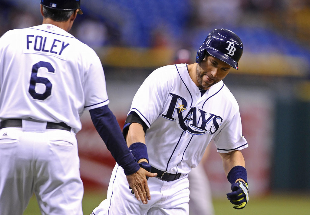 . Tampa Bay Rays\' Luke Scott, right, celebrates with third base coach Tom Foley as he rounds the bases after hitting a solo home run off of Minnesota Twins starting pitcher Samuel Deduno during the first inning. (AP Photo/Brian Blanco)