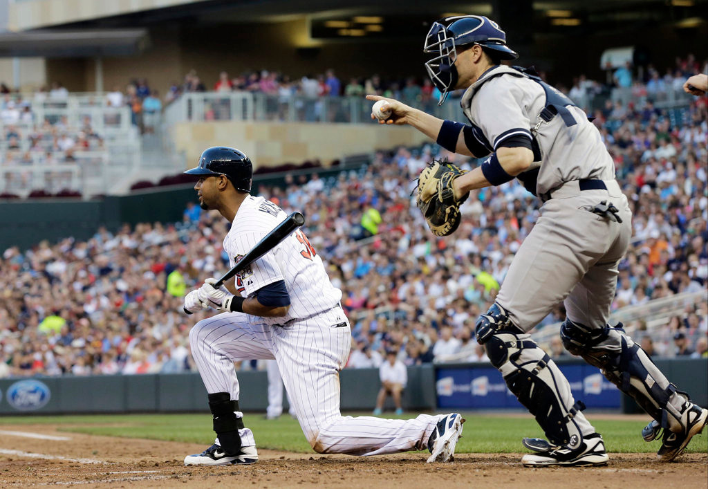 . Yankees catcher Chris Stewart, right, gestures to pitcher Phil Hughes after Minnesota Twins\' Aaron Hicks struck out in the fourth inning. (AP Photo/Jim Mone)