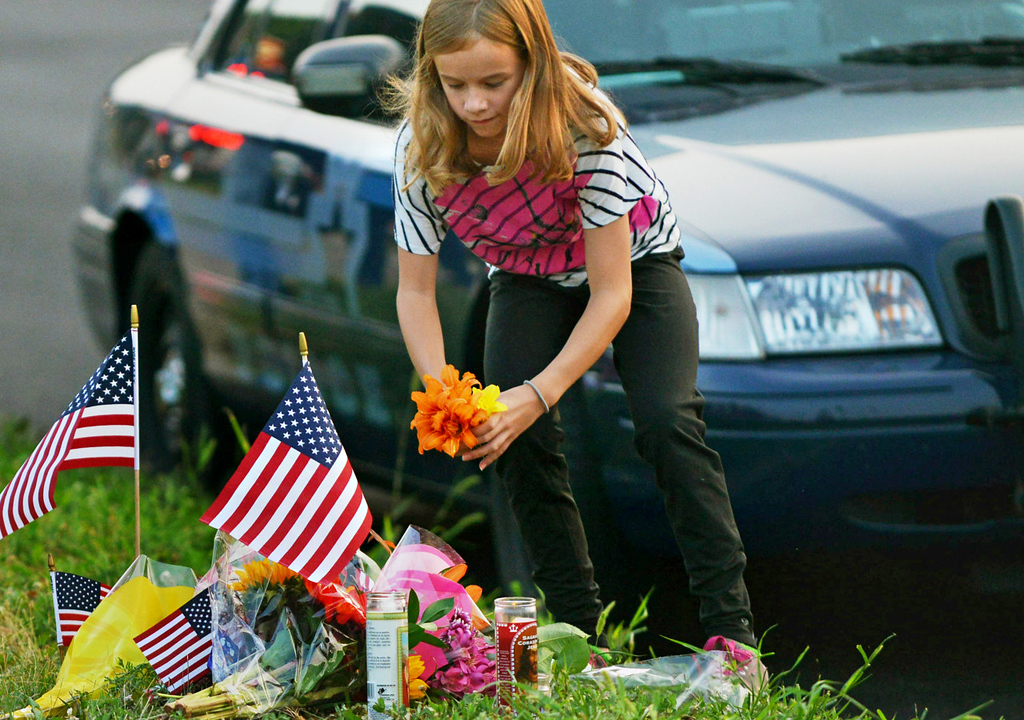 . A young girl adds flowers to a memorial for slain Mendota Heights Police Officer Scott Patrick before a candlelight vigil in his honor on Wednesday night. (Pioneer Press: John Autey)