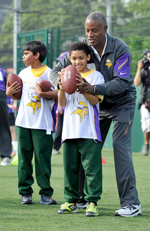 . Vikings quarterback coach Craig Johnson works with youth during a football clinic. (NFL: Sean Ryan)