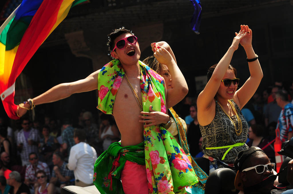 . A man waves a rainbow flag as he celebrates along with the Shades of Yellow Hmong LGBTQ group at the annual Twin Cities Pride Parade along Hennepin Avenue in downtown Minneapolis on Sunday, June 30, 2013. (Pioneer Press: Scott Takushi)