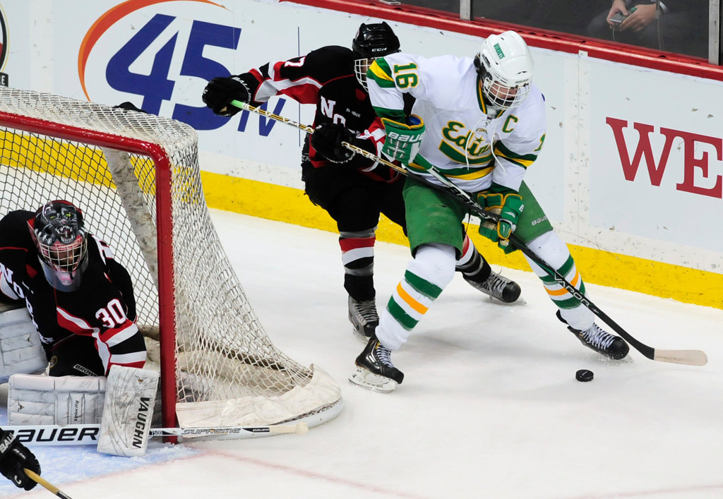 . Edina\'s Connor Hurley is pursued by Lakeville North\'s Angelo Altavilla as he works the puck toward goalie Will DuPont in the third period. (Pioneer Press: Scott Takushi)