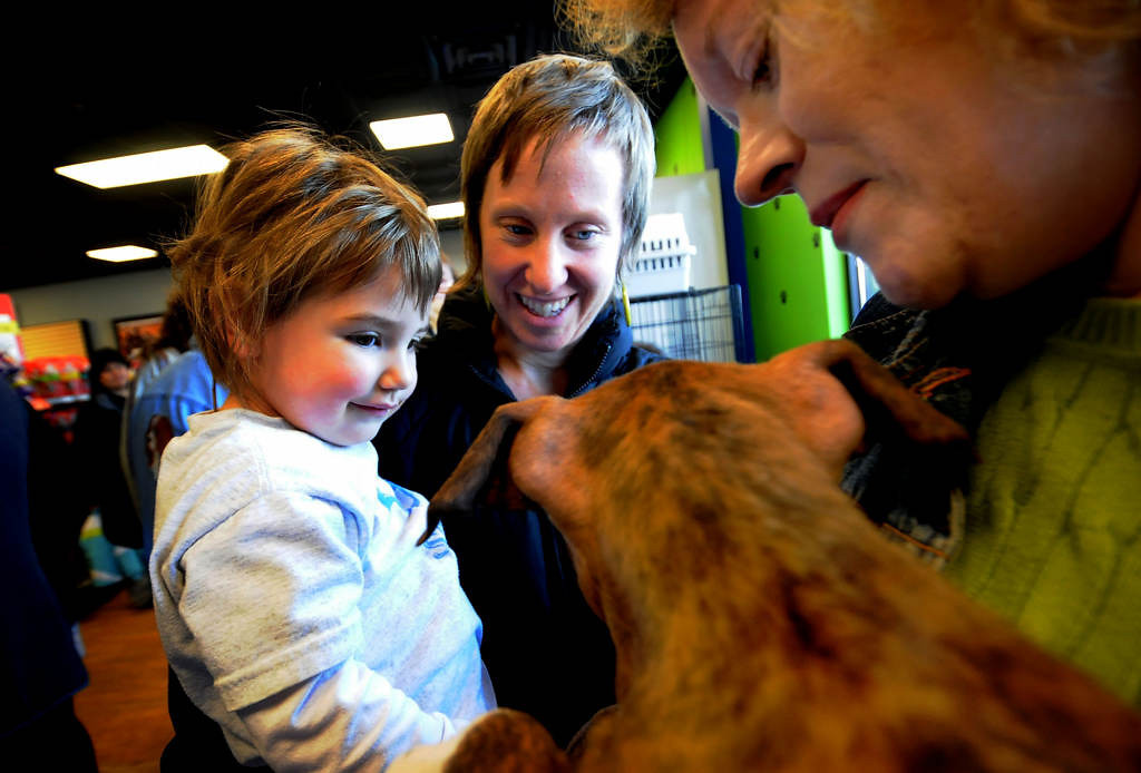 . Laura Thielges, left, and her daughter Lucia, of Maplewood a puppy named Phoenix, held by Deb Stevens of Bloomington, during a pet adoption event at Pet Evolution in Woodbury on Saturday, Feb. 16, 2013.  (Pioneer Press: Sherri LaRose-Chiglo)