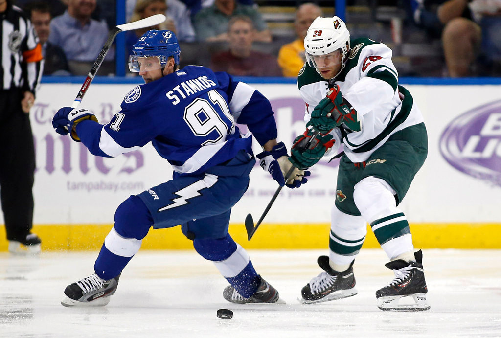 . Steven Stamkos #91 of the Tampa Bay Lightning and Jason Pominville #29 of the Minnesota Wild battle for a loose puck.  (Photo by Mike Carlson/Getty Images)