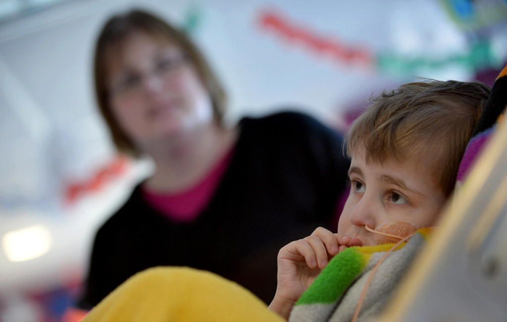 . Cameron Ulrich watches a cartoon alongside his mom Kari, left, in his room.   (Pioneer Press: Richard Marshall)