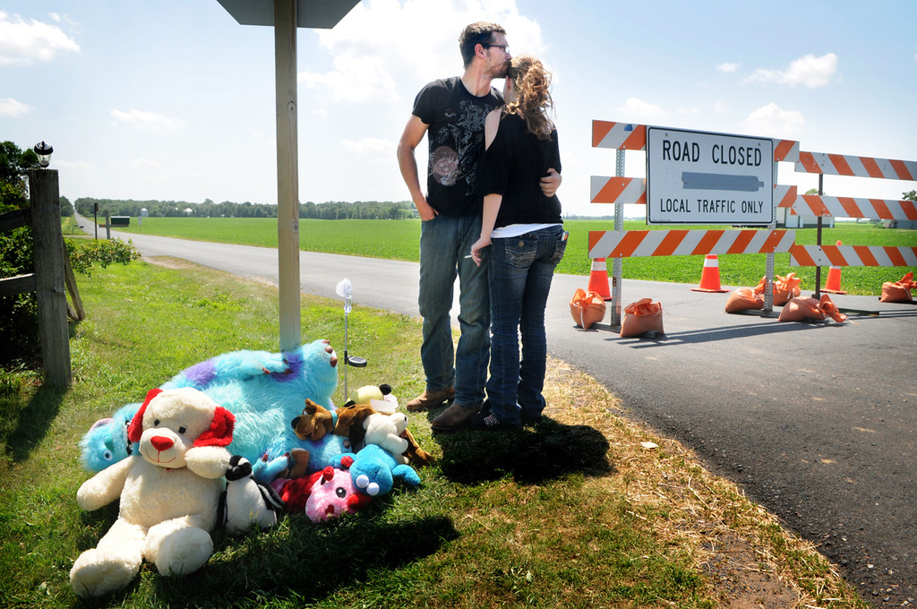 . Adam Pool hugs his wife, Charlene Shepherd, after they put a stuffed animal and candy at a memorial for 2-year-old Isaiah Theis in Centuria, Wis., on Thursday, July 18, 2013. The body of Isaiah, who went missing Tuesday night, was found late Wednesday in the trunk of a car. Pool and his wife, who are from Williston, N.D., were in Centuria on vacation and were among the many volunteers who helped with the search. (Pioneer Press: Jean Pieri)
