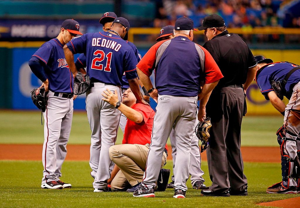 . Pitcher Samuel Deduno #21 of the Minnesota Twins is examined by a trainer in the second inning after he is hit by a line drive against the Tampa Bay Rays. (Photo by J. Meric/Getty Images)
