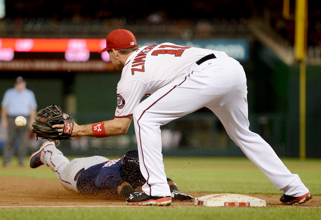 . Minnesota Twins second base Eduardo Escobar (5) slides head first safely into third base, before the throw reaches Washington Nationals third baseman Ryan Zimmerman (11), on a triple in the sixth inning of the second game of a day-night doubleheader.(Chuck Myers/MCT)