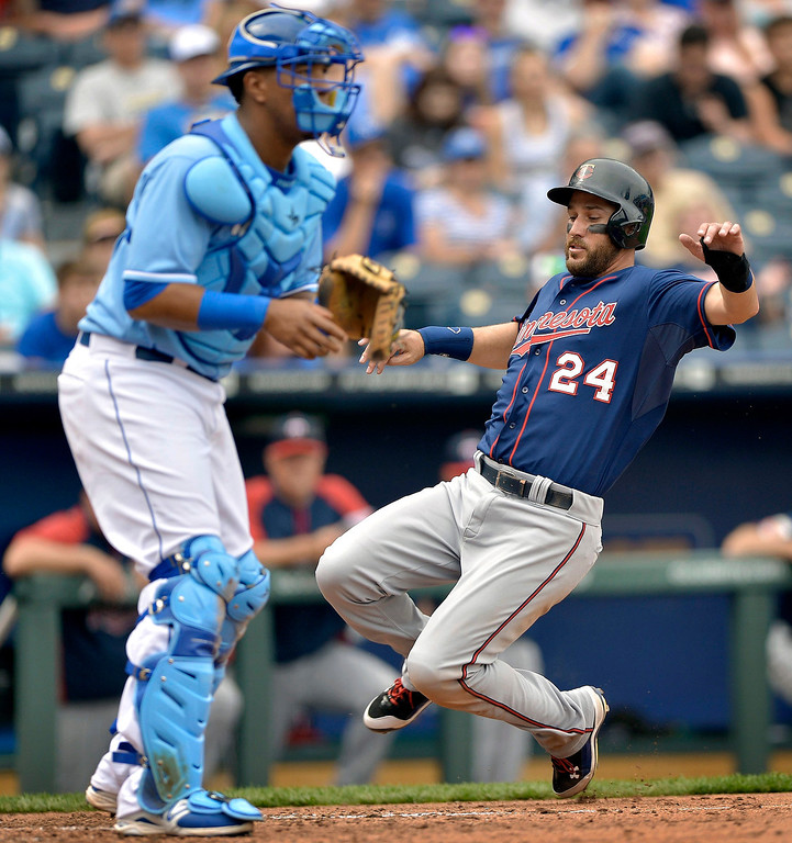 . The Minnesota Twins\' Trevor Plouffe (24) scores as Kansas City Royals catcher Salvador Perez (13) looks for the throw in the seventh inning. (John Sleezer/Kansas City Star/MCT)