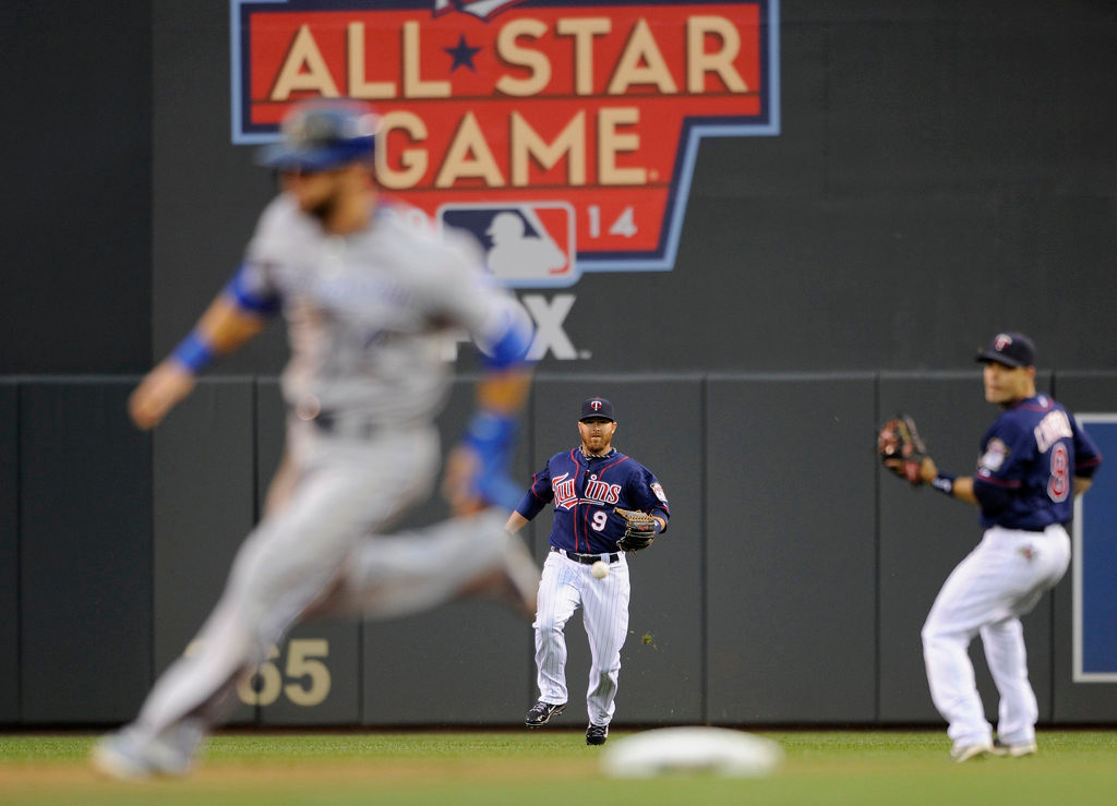 . Alex Gordon #4 of the Kansas City Royals rounds second base as the baseball hit by teammate Salvador Perez  falls in between Ryan Doumit #9 and Jamey Carroll #8 of the Minnesota Twins during the first inning.  (Photo by Hannah Foslien/Getty Images)