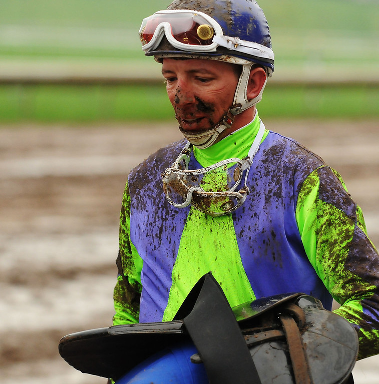 . Jockey Dean Butler is covered with mud after riding T. Thomas in the first race. (Pioneer Press: John Autey)