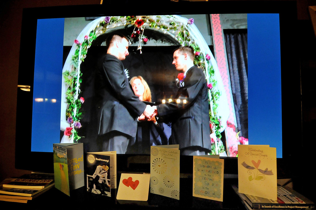 . Anniversary and wedding cards for Ryan Pfeifle and Bradley Weber are lined up in front of a television set showing images from their commitment ceremony 10 years ago. (Pioneer Press: Sherri LaRose-Chiglo)
