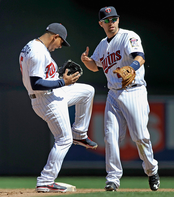 . Twins players Eduardo Escobar, left, does a jig alongside teammate Brian Dozier as they celebrate their 10-0- win against the Seattle Mariners on Sunday. (Photo by Hannah Foslien/Getty Images)