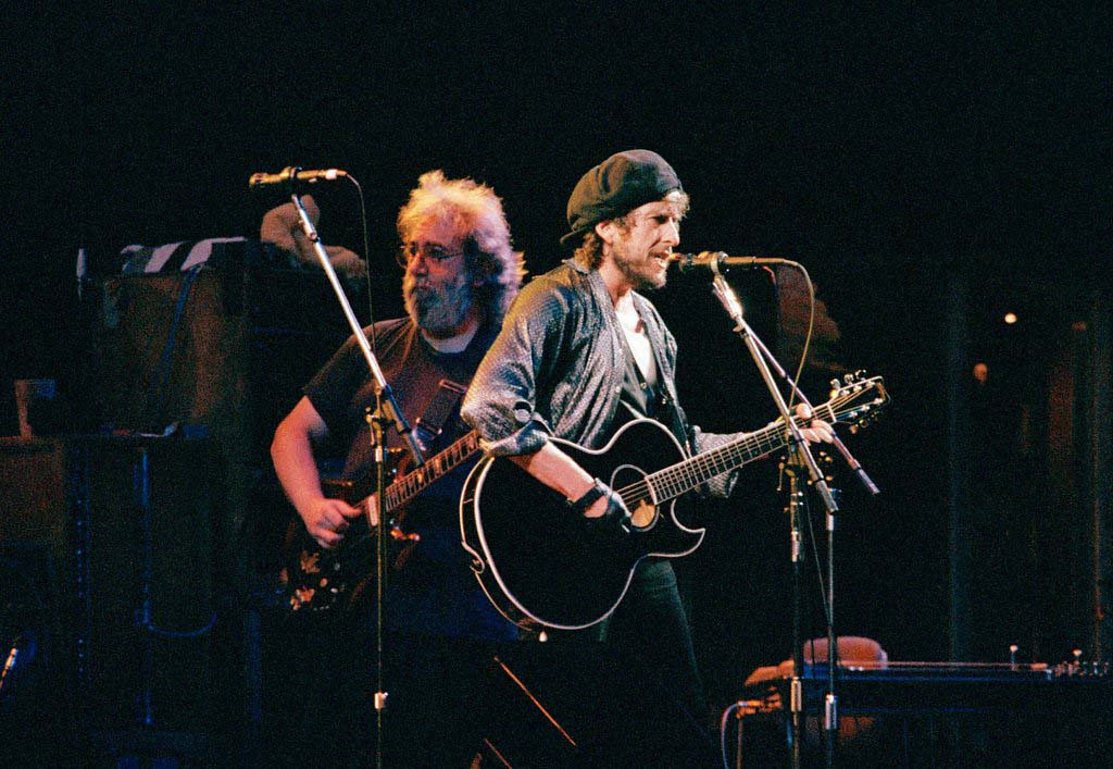 . Bob Dylan , right, is accompanied by the Grateful Dead guitarist Jerry Garcia during the Grateful Dead Bob Dylan concert at Giants Stadium in East Rutherford, N.J., July 13,1987. (AP Photo/Tom Costello)