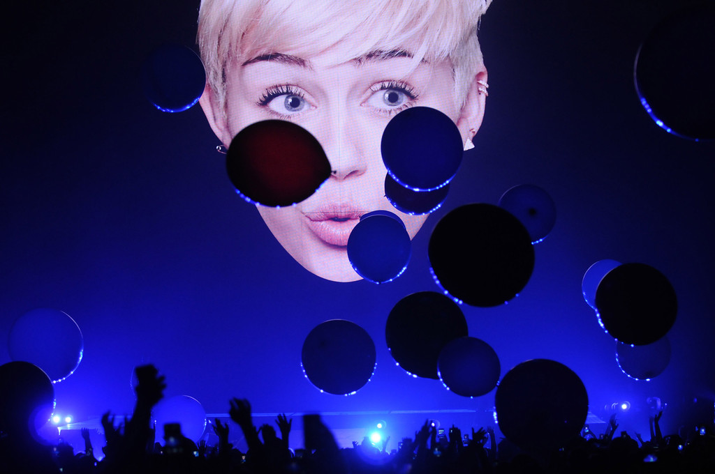 . A huge projection of Miley Cyrus\'s face hovers over the stage before the star of the show appears. (Pioneer Press: Scott Takushi)
