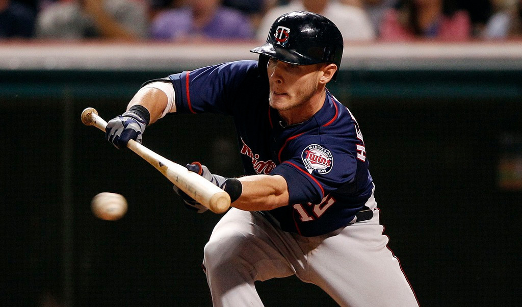 . Minnesota\'s Chris Herrmann drops down a bunt during the seventh inning against the Indians, advancing base runner Brian Dozier to third.  (Photo by David Maxwell/Getty Images)