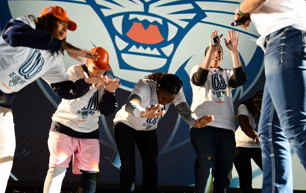 . Lynx players (from left) Seimone Augustus, Lindsay Whalen, Rebekkah Brunson and Janel McCarville bow down towards Maya Moore after she spoke to the crowd during the team\'s WNBA championship pep rally.  (Pioneer Press: Ben Garvin)