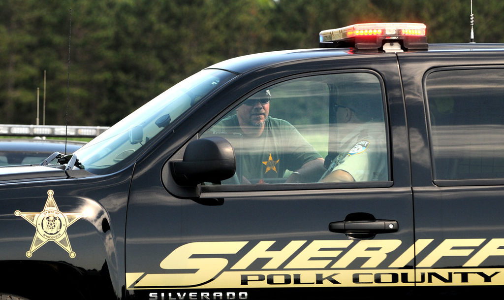 . Polk County sheriff\'s deputies talk to each other at the 180th Street barricade in Centuria, Wis., near the location where the body of 2-year-old Isaiah Theis was found. (Pioneer Press: Jean Pieri)