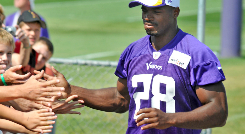 . Vikings running back Adrian Peterson slaps a whole bunch of welcoming hands as he enters the field at the start of morning drills during training camp in Mankato on Wednesday, Aug.t 6, 2013.   (Pioneer Press: John Doman)