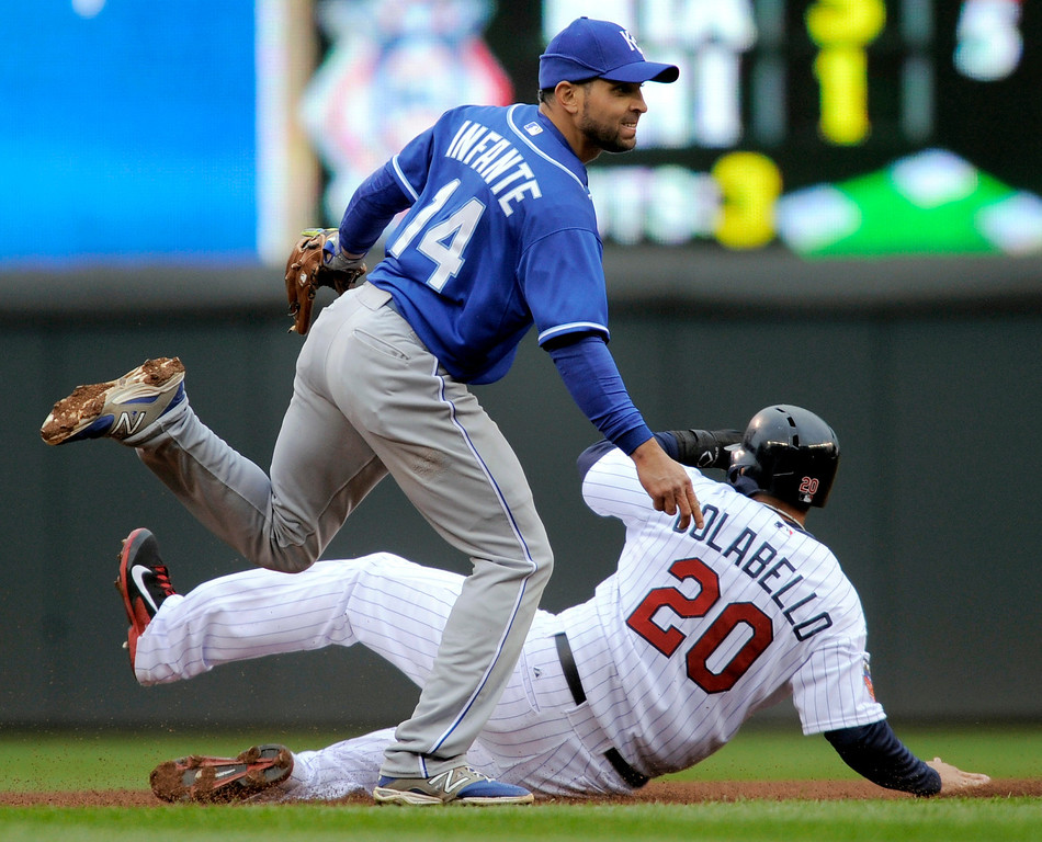 . Kansas City Royals second baseman Omar Infante, left, steps over the sliding Minnesota Twins Chris Colabello (20) after getting the force at second during the fourth inning. Josmil Pinto was out at first. (AP Photo/Tom Olmscheid)